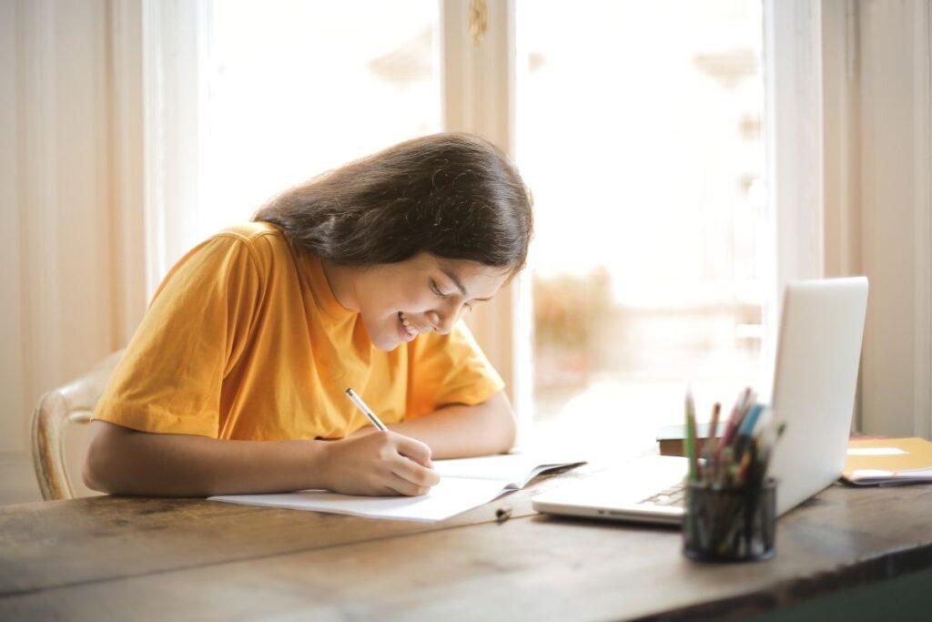 tanara cu parul lung saten imbracata in tricou galben sta la birou si scrie exercitii