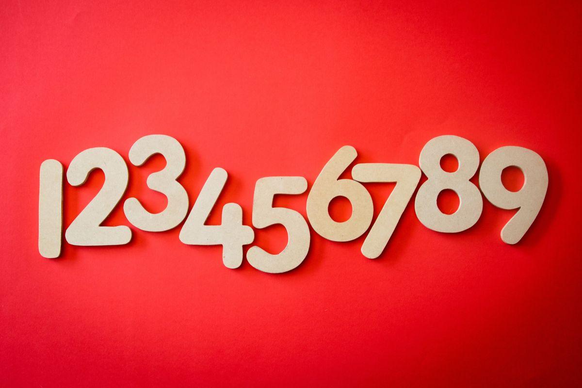 numerele de la 1 la 9 din lemn natur in rand pe fundal rosu
