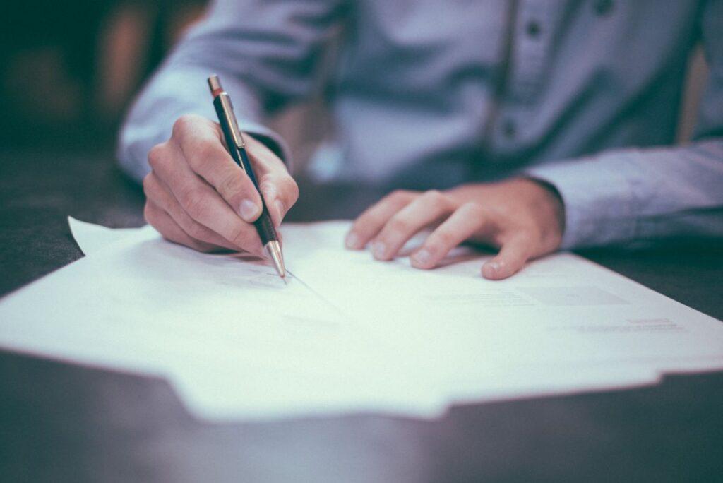 om de afaceri imbracat business semneaza o scrisoare oficiala cu pixul