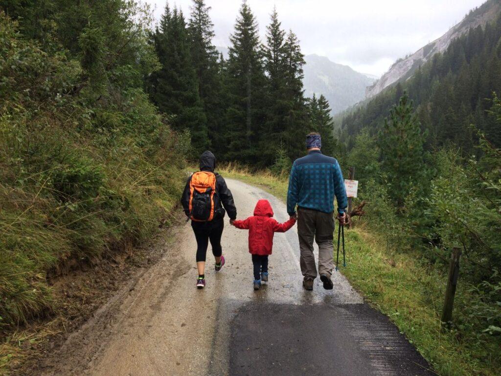 Copil tinut de manute de cei doi parinti imbracati sportiv se plimba in fata pe un drum de munte incadrat de brazi si tufisuri