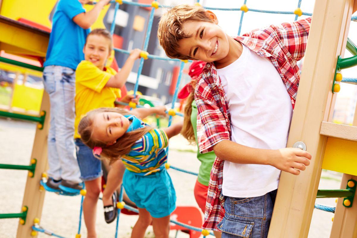 copii de varste diferite imbracati colorat care se catara pe funii la un loc de joaca, privind zambitori spre camera