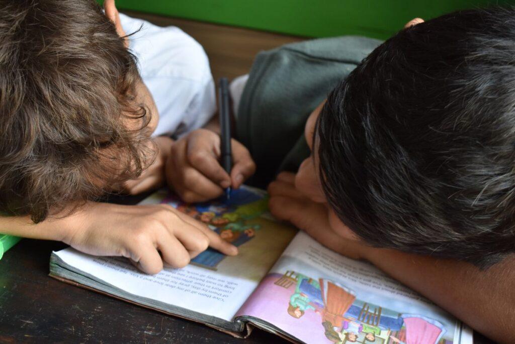 Doi copii lucreaza in pereche la un curs de engleza pentru a intelege o poveste dintr-o carte