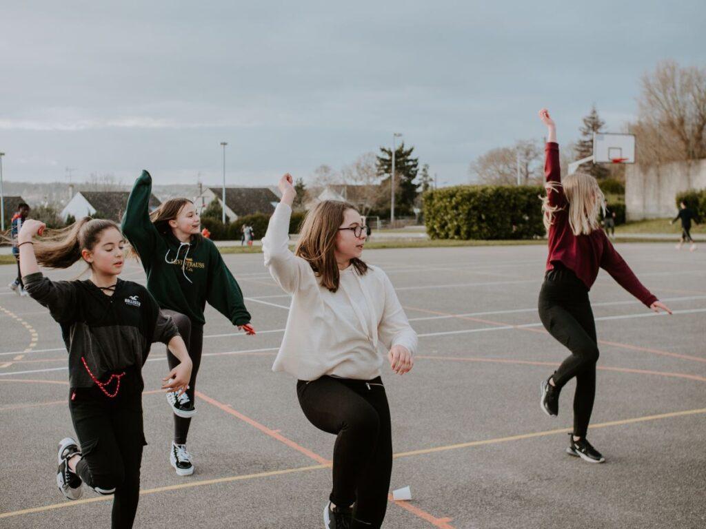 patru fete participa la un curs de dans in aer liber si imita miscarile instructoarei
