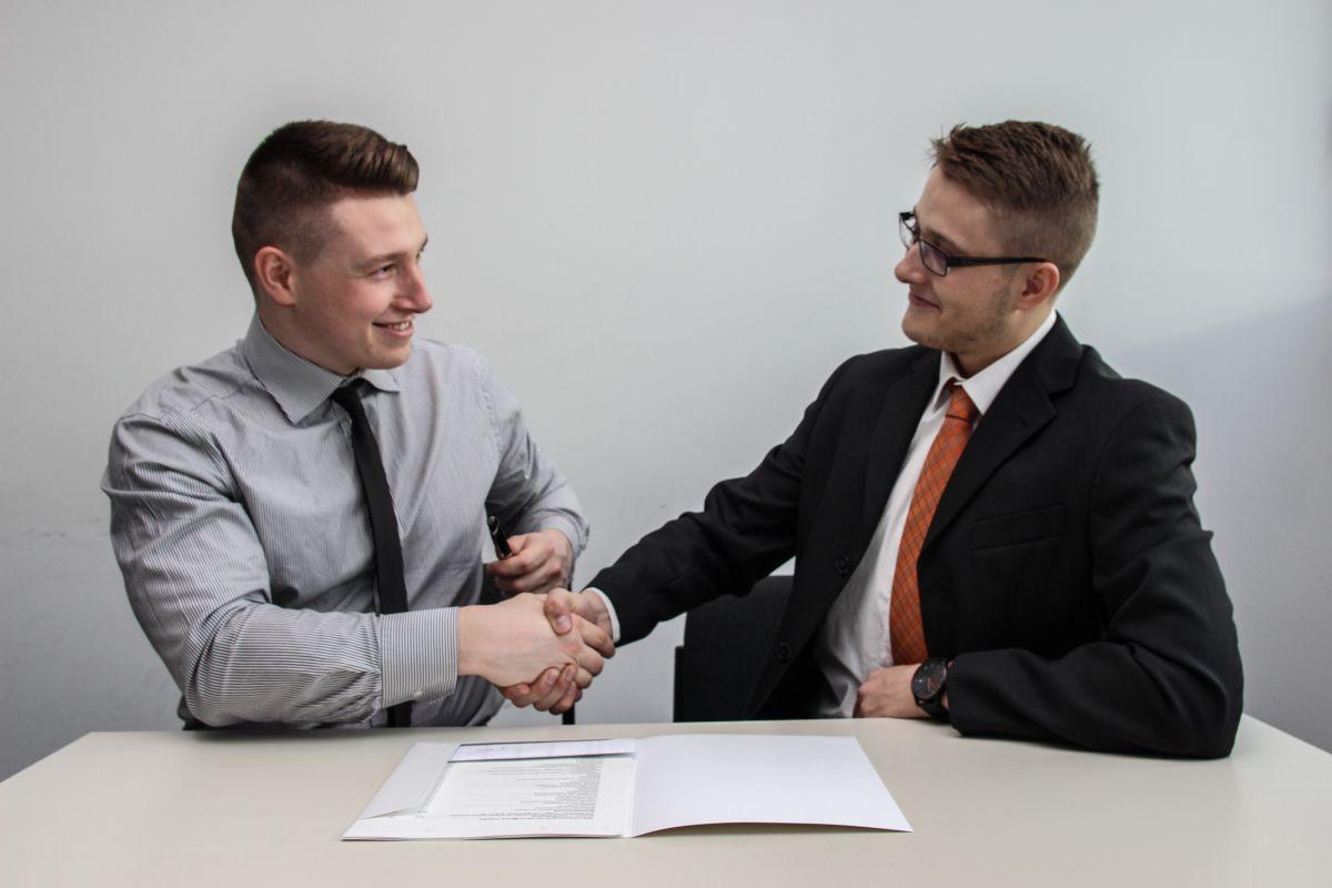 Un recrutor si un candidat la un post isi strang mana deoarece au ajuns la o intelegere in urma unui interviu in limba engleza, pe birou in fata lor fiind CV-ul in engleza al candidatului
