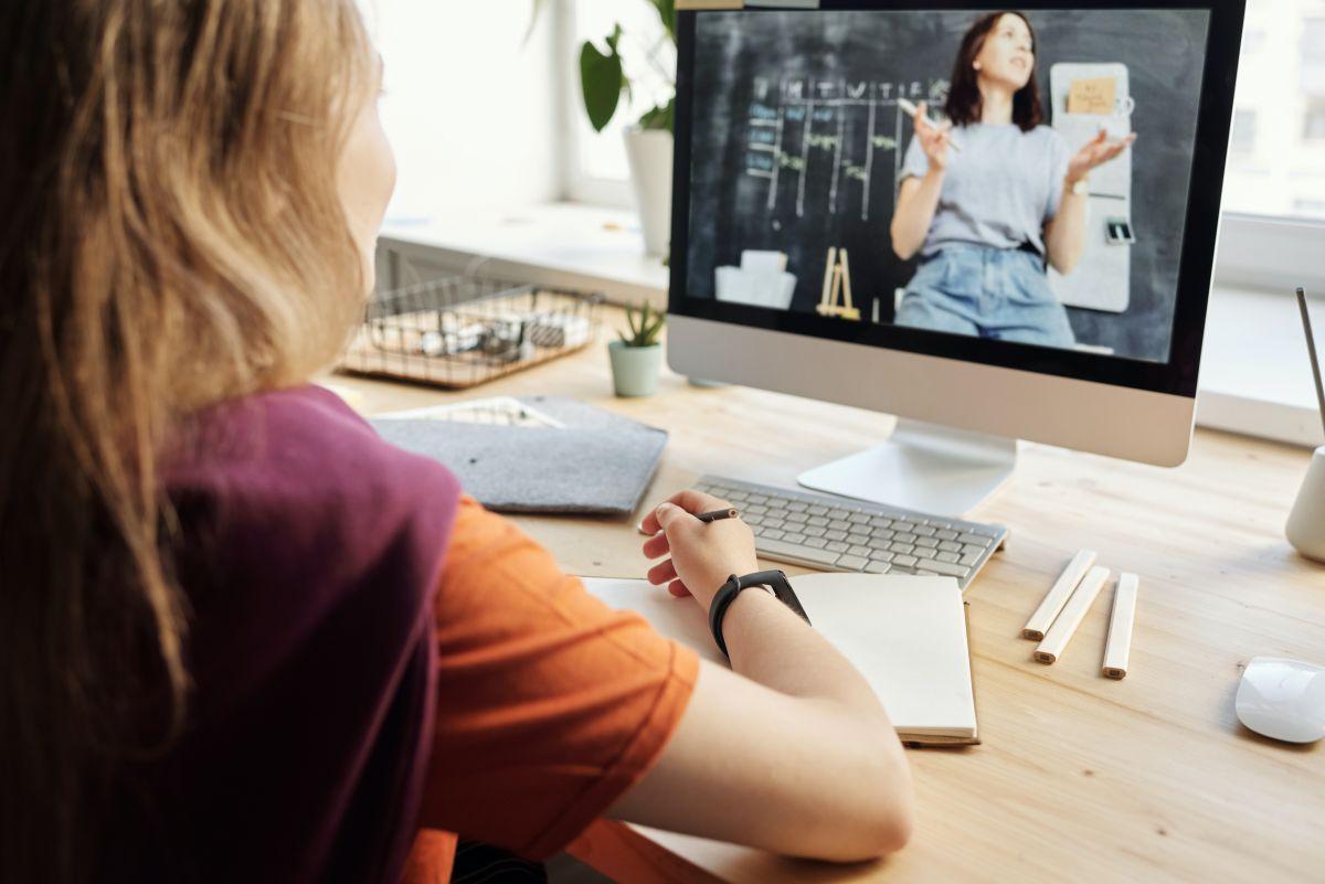 Tanara in fata monitorului o priveste pe profesoara ei la un curs online