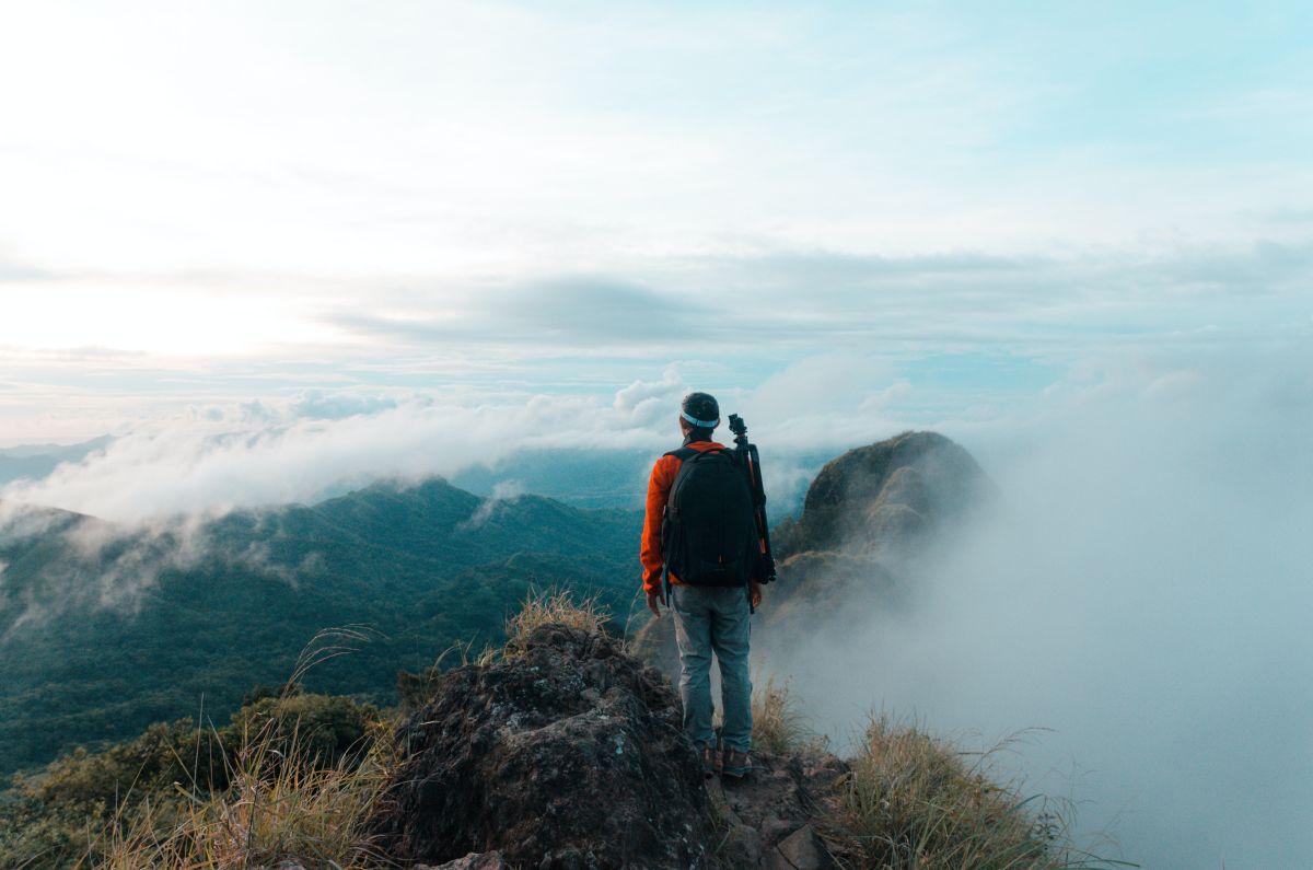 Barbat imbracat sportiv cu spatele sta in picioare in varful unui munte deasupra norilor