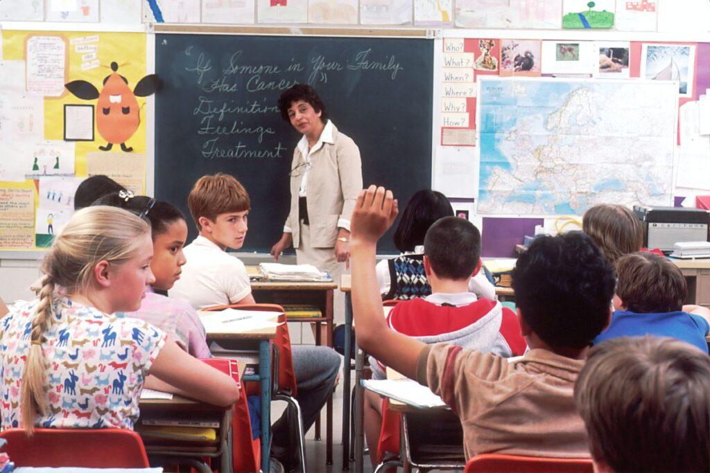 grupa de curs de engleza discuta cu profesoara care e in fata tablei un subiect delicat precum bolile maligne