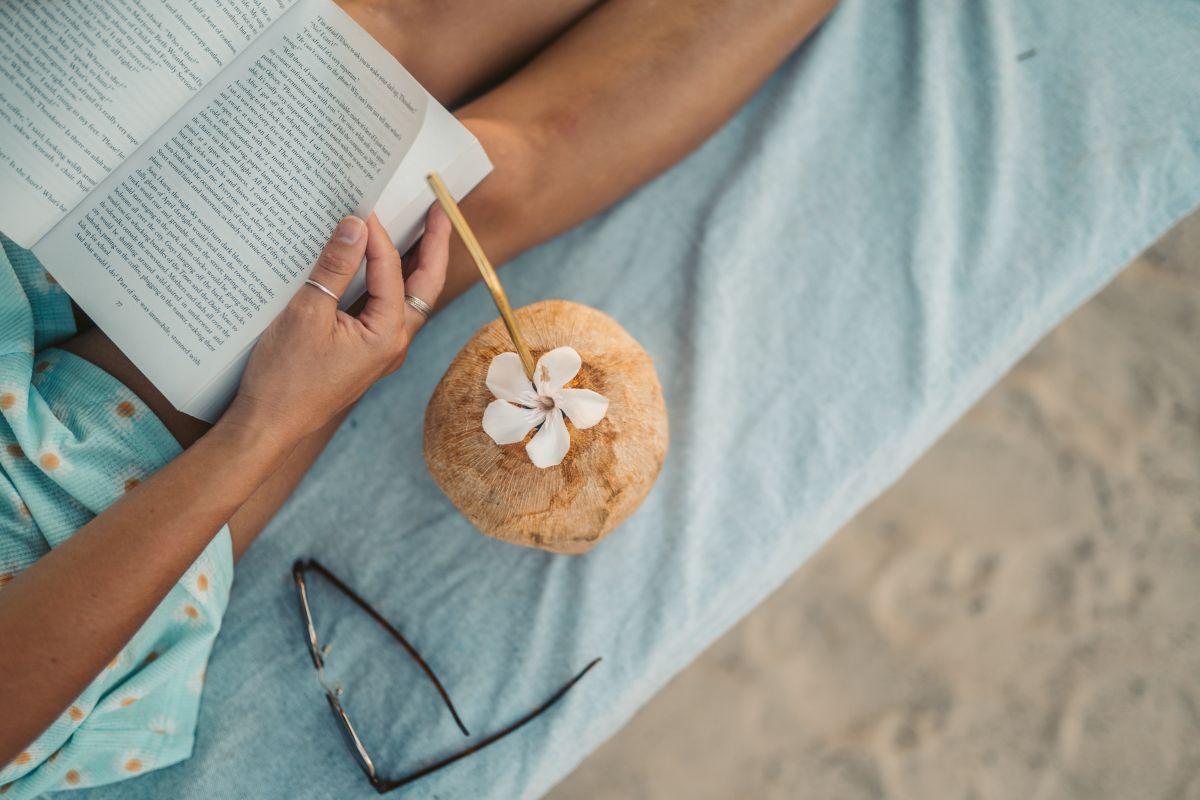 persoana asezata pe o saltea pe plaja care citeste o carte in limba engleza