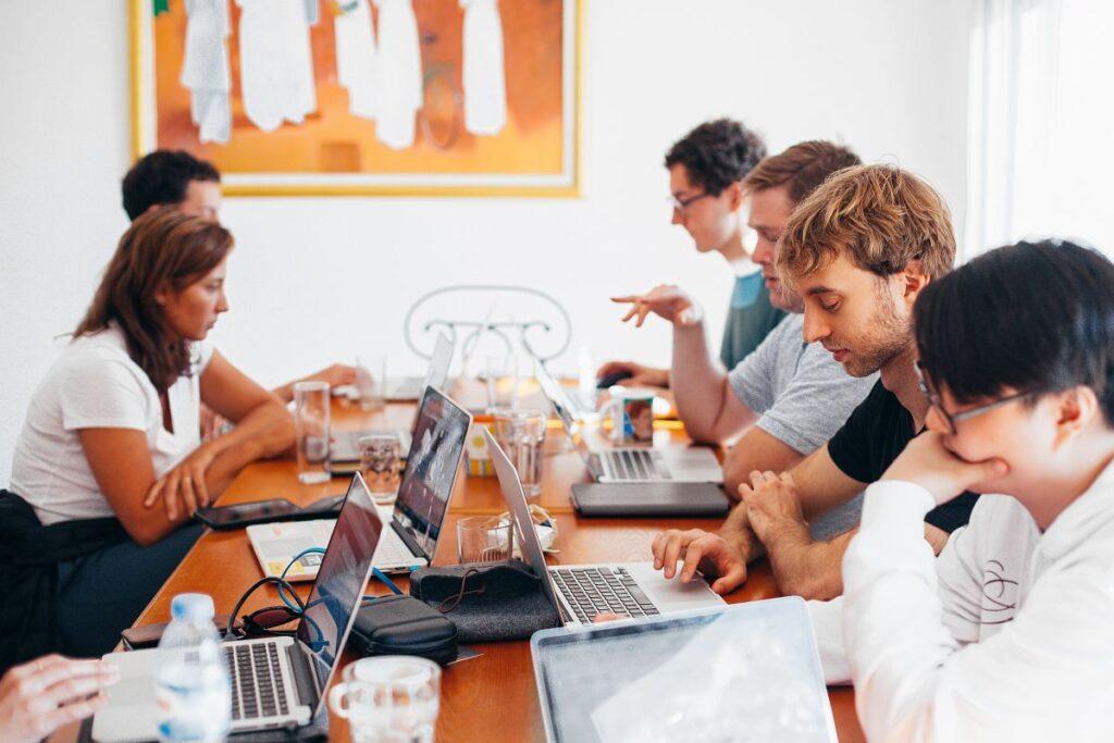 Tineri care lucreaza la laptopuri si participa la un eveniment online in limba engleza